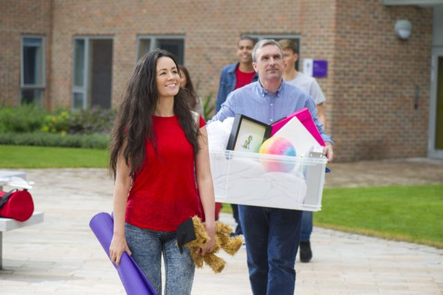 Man carrying a bin of pictures walking on a sidewalk with a young woman walking next to him carrying a yoga mat and a small teddy bear with a graduation cap on it.